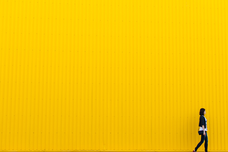 Woman Walking in front of large yellow wall | Image