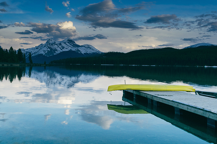 Upside down canoe on a pier with a mountain in the background | Image