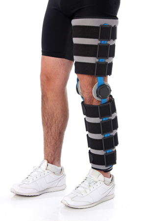 A man with a foot-to-hip blue leg brace on. Physio