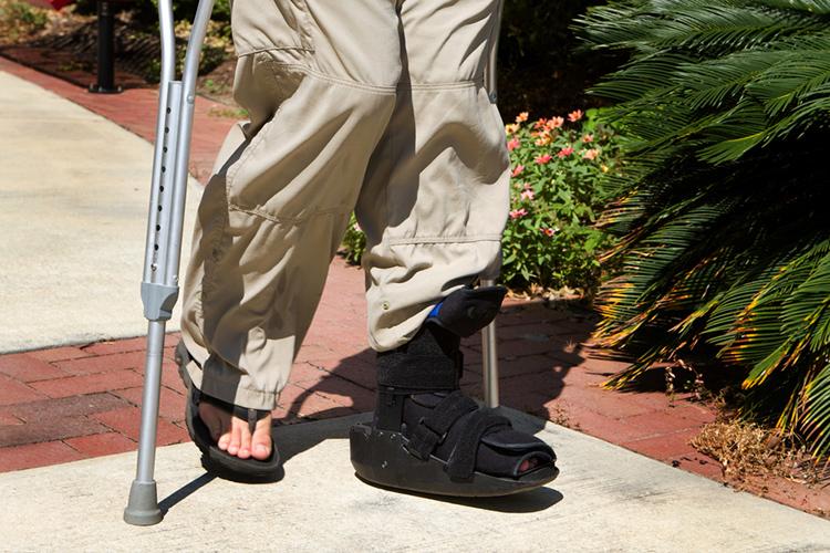 A woman walking in a leg brace. Physio