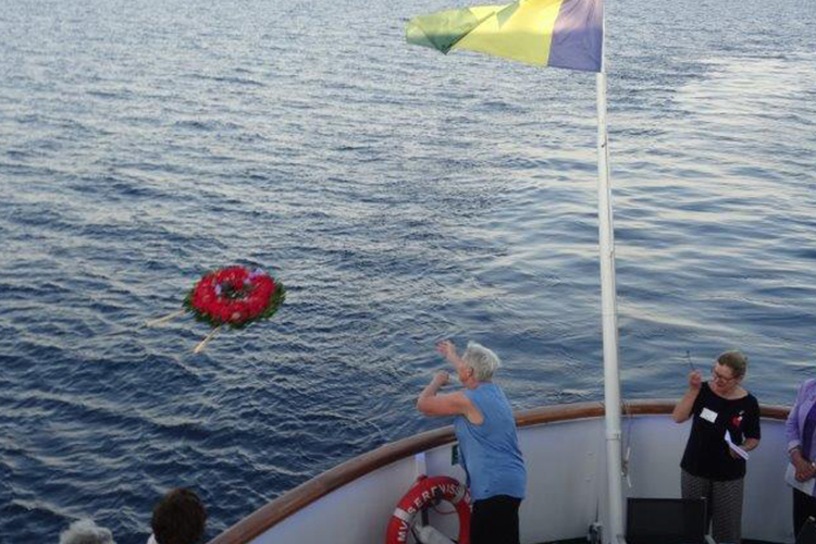 A large wreath of red carnations being thrown into the sea. - ANZAC