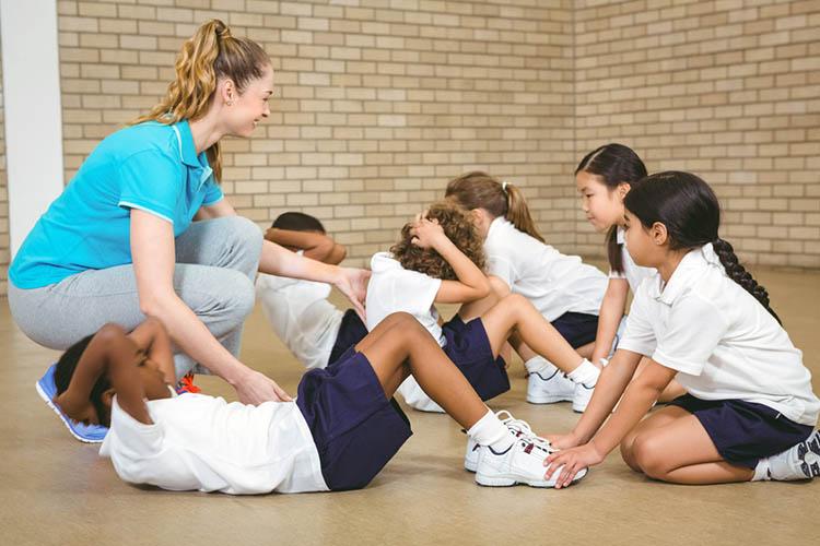 Children exercising with teacher