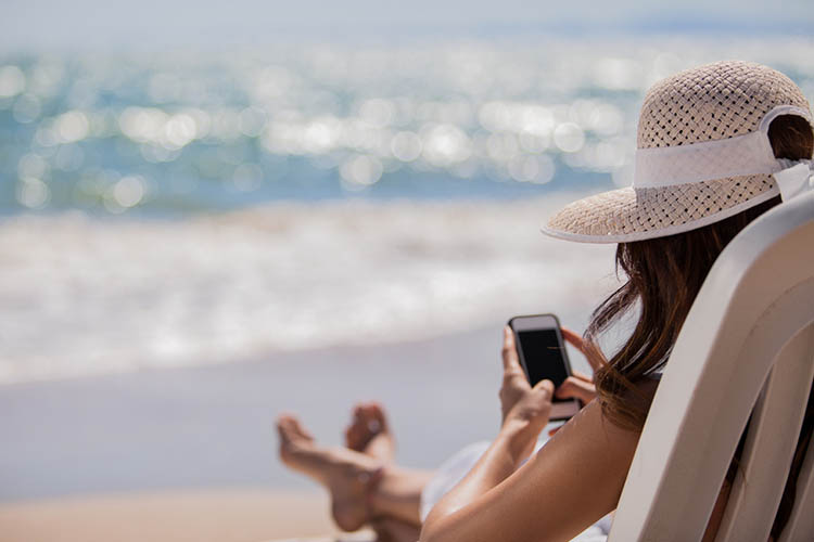 Woman on phone at beach | Image