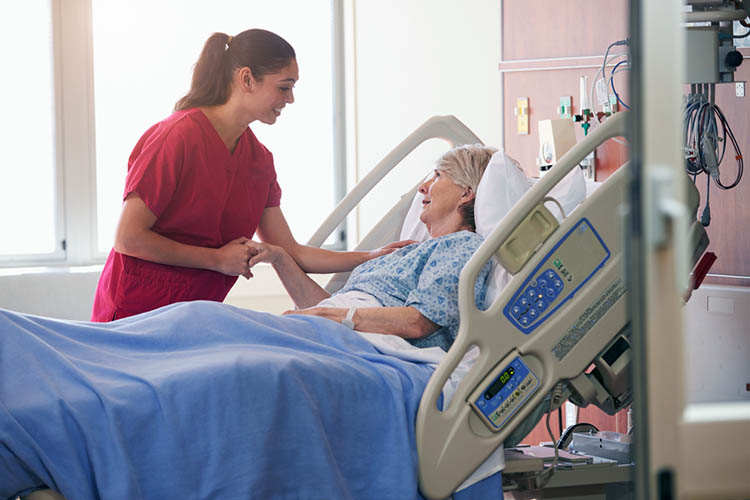 Nurse comforting elderly patient in hospital bed | Image