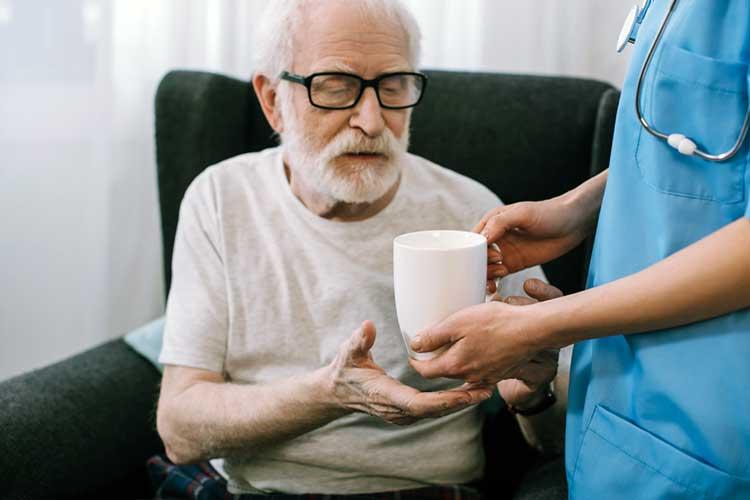 Elderly man receiving a beverage in a mug from a nurse | Image