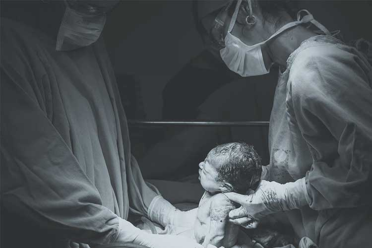 Two doctors holding a baby sitting up after birth | Image