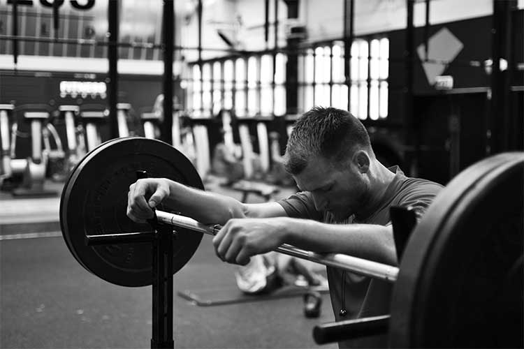 Man looking down with arms resting on a barbell whilst resting | Image