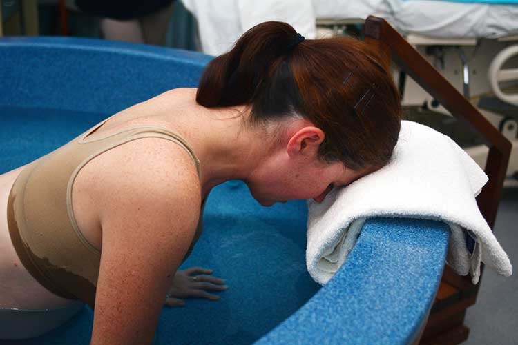Woman with her head pressed on a towel in a water birthing pool preparing to birth | Image
