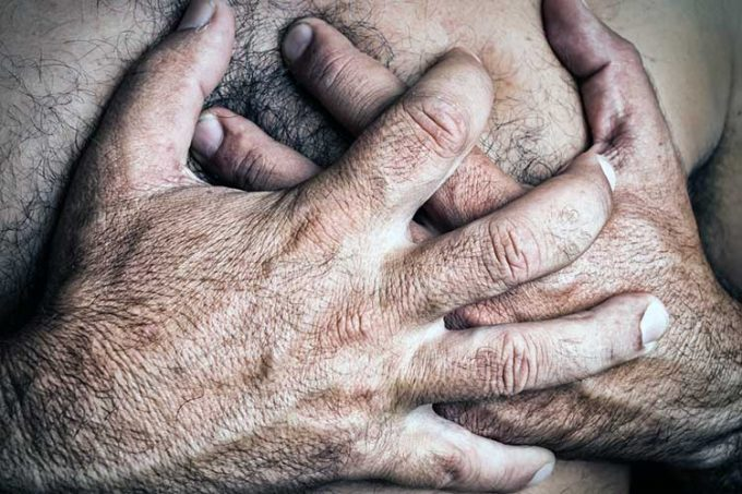 Man holding his chest due to a heart attack or stroke