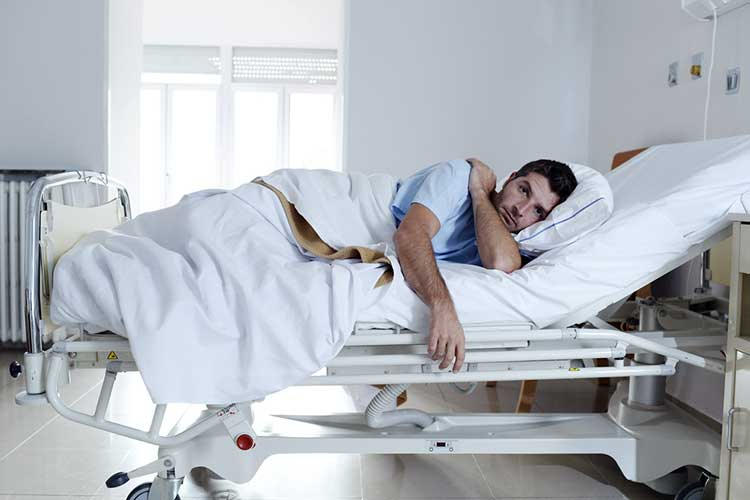 Male patient lying on his side in a hospital bed | Image