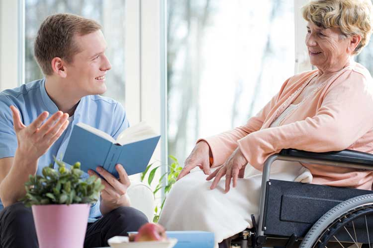 Male healthcare worker reading a book to an elderly female woman | Image