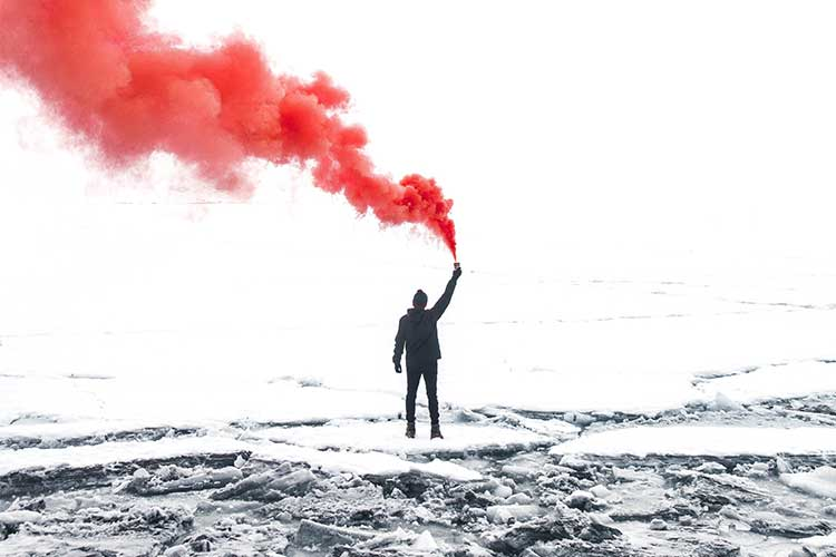 Person holding a flare with red smoke | Image