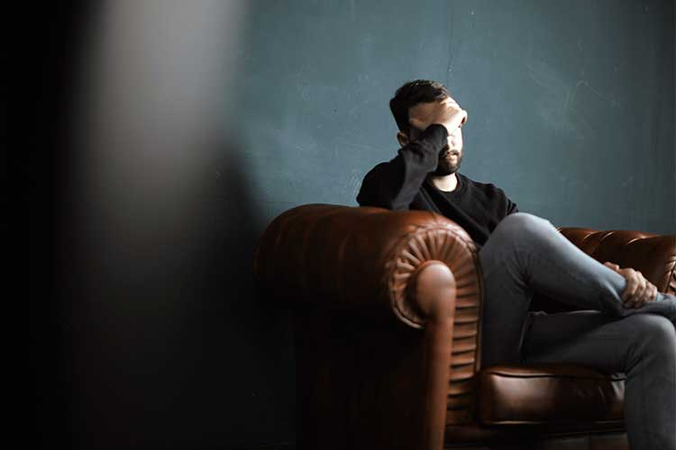 Man sitting in a chair with his hand on his face in shame | Image