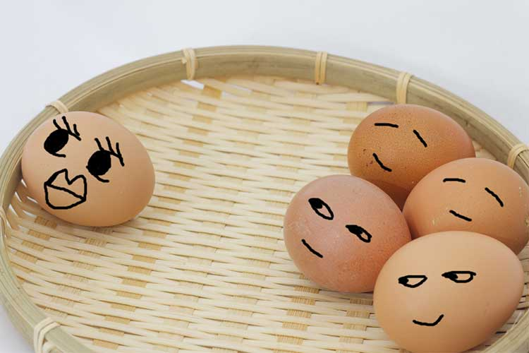 Concept of tall poppy syndrome using eggs in a basket with faces drawn on them | Image